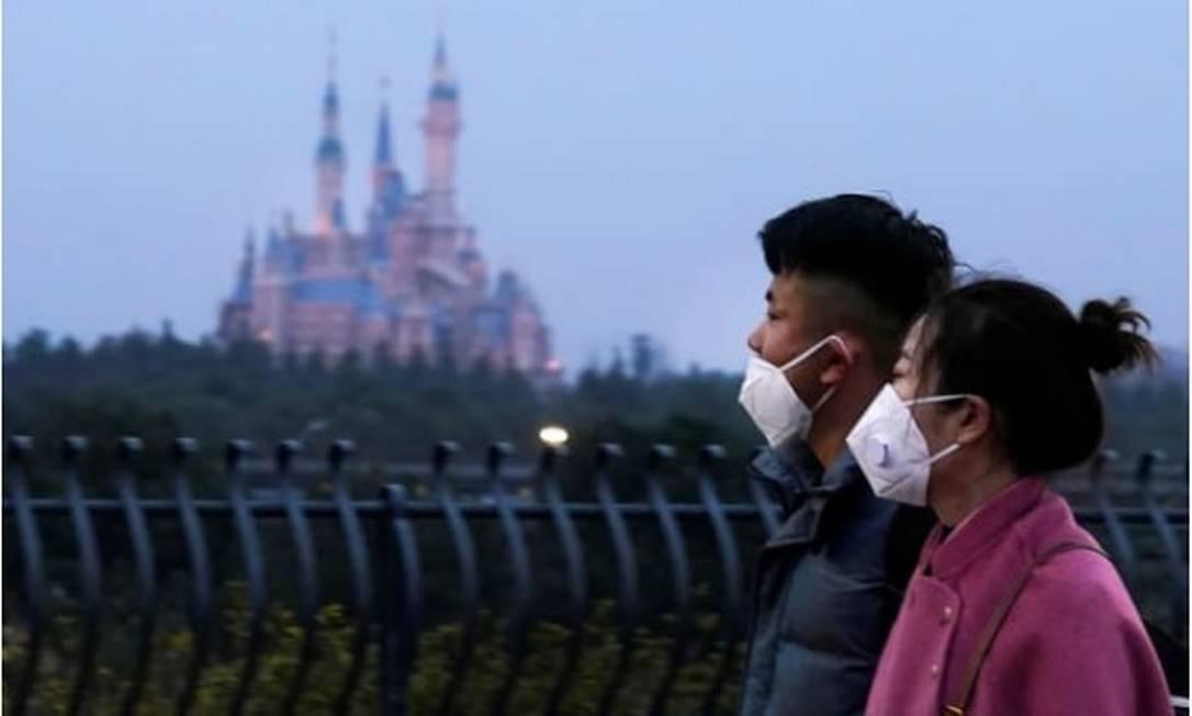 Vsitantes usando máscaras passam pelo Shanghai Disney Resort, na China. Foto: Reuters