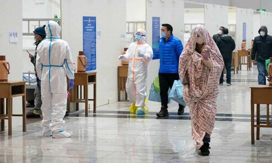 Paciente infectado pelo coronavírus, enrolado em um cobertor, chega em hospital temporário instalado dentro de um centro de exposições da cidade de Wuhan Foto: Getty Images