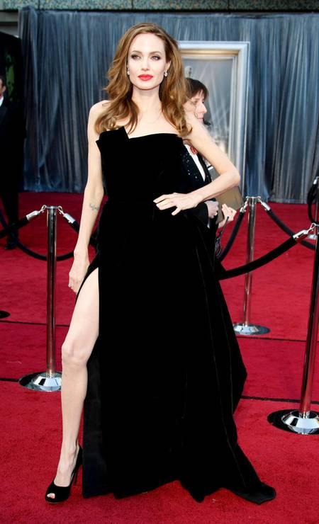 Angelina Jolie não podia ficar de fora da lista de melhores looks com o clássico vestido preto da Versace e sua profunda fenda, que ela aproveitou o máximo que pôde. O visual femme fatale foi o mais comentado naquele ano. Foto: Dan MacMedan / WireImage