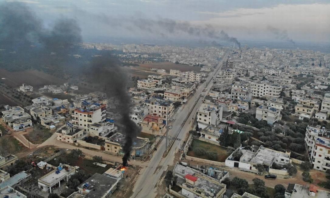 Vista aérea da fumaça subindo dos pneus queimados pelos sírios na tentativa de impedir ataques aéreos, em meio a confrontos na cidade de Binnish, na província de Idlib, no noroeste da Síria. Foto: OMAR HAJ KADOUR / AFP
