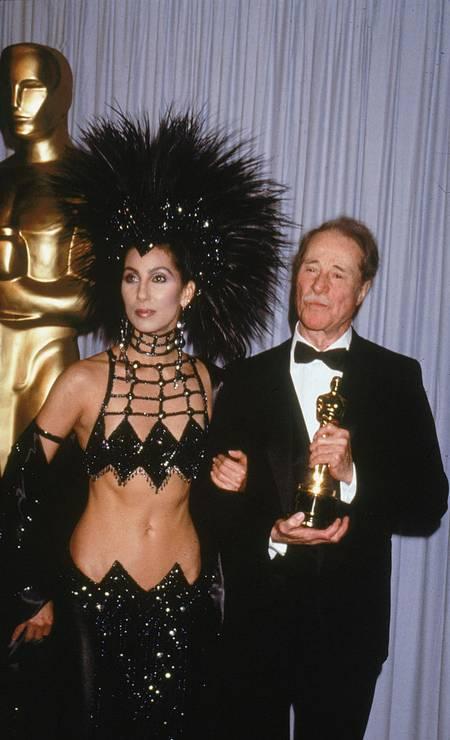 Falando em escola de samba, esse look escolhido por Cher em 1986 podia muito bem ter sido usado em uma escola de samba. O top e a saia foram criados pelo estilista americano Bob Mackie. Foto: Darlene Hammond / Getty Images
