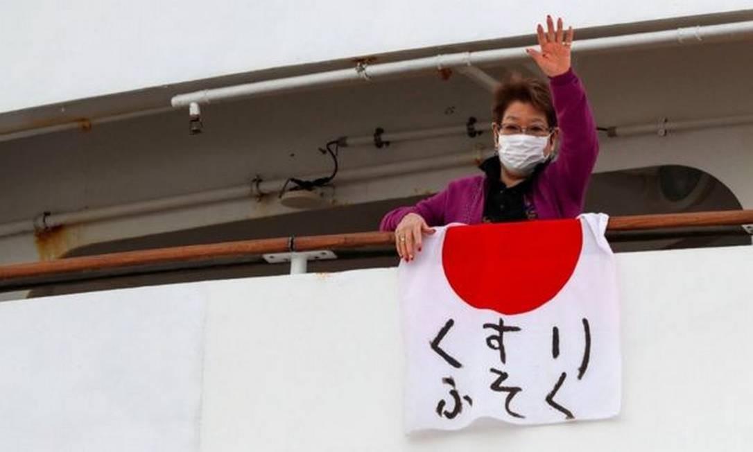 Passageira do cruzeiro Dream Princess exibe bandeira japonesa com alerta sobre falta de remédios Foto: Reuters