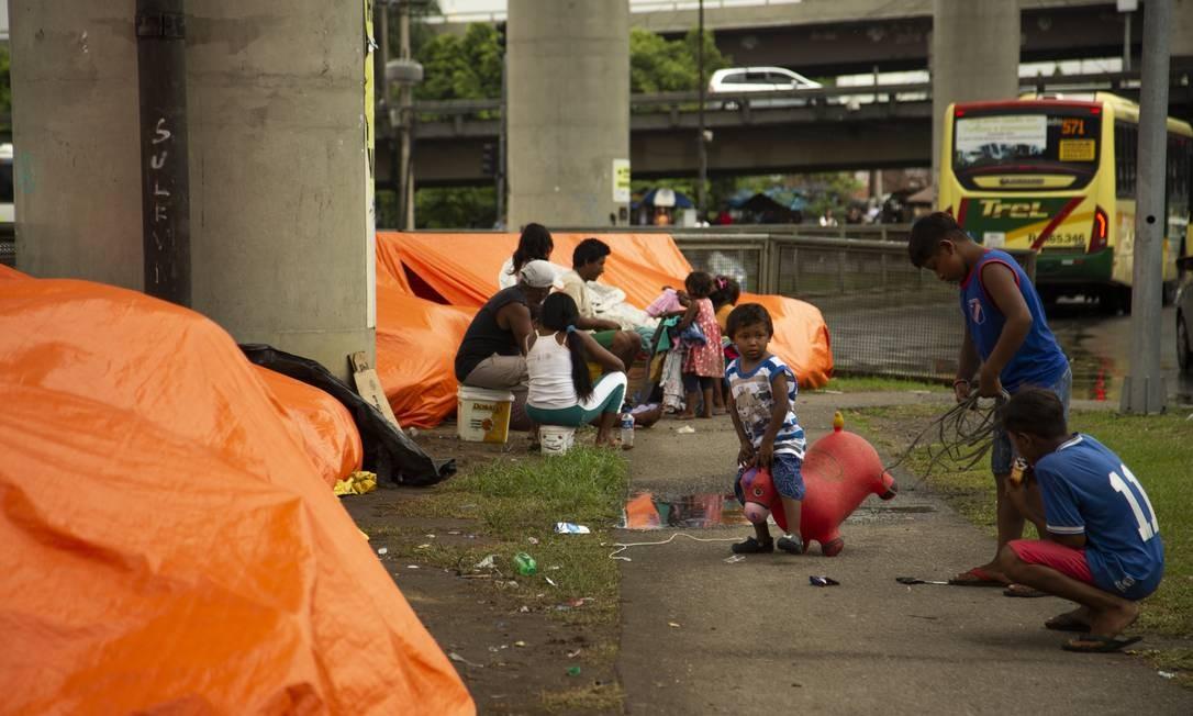 Cerca de dez tendas amarradas ao gradil que divide uma movimentada via da calçada de pedestres viraram casa para 27 indígenas venezuelanos que vivem, na condição de refugiados, nos arredores da Rodoviária Novo Rio Foto: Gabriel Monteiro / Agência O Globo
