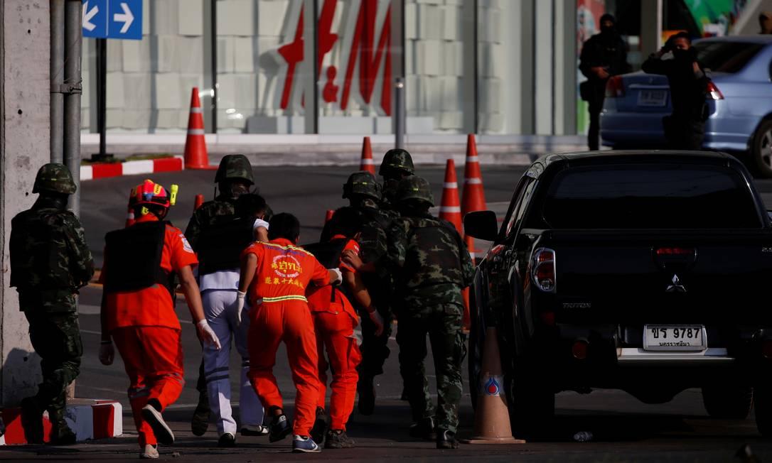 Policiais protegem paramédicos na entrada do shopping tailandês onde um militar se refugiou após matar 21 pessoas Foto: SOE ZEYA TUN / REUTERS