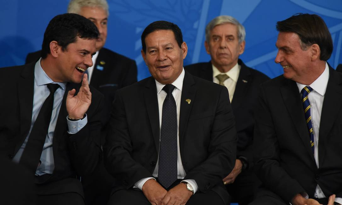 O ministro Sergio Moro conversa com o vice Hamilton Mourão e o presidente Bolsonaro na cerimônia de assinatura do decreto que muda Conselho da Amazônia Foto: FramePhoto / Agência O Globo