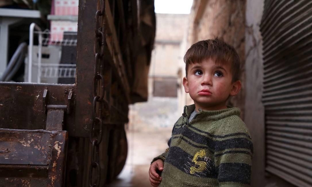 Criança síria enquanto familiares colocam seus pertences em caminhão para deixar a província de Idlib, onde grupos armados atuam contra o regime de Bashar al-Assad Foto: AAREF WATAD / AFP