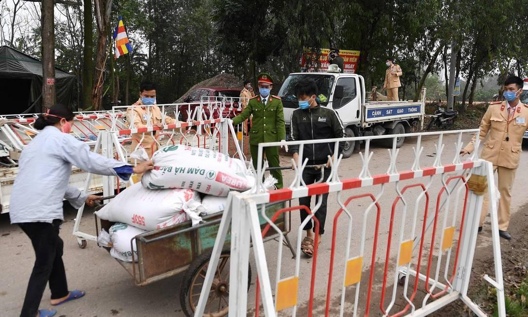 Policiais de máscara deixam moradora entrar com mercadorias em Son Loi, cidade de 10 mil habitentes que entrou em quarentena Foto: NHAC NGUYEN / AFP