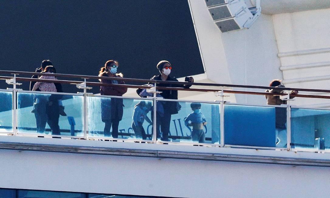 Passageiros com crianças do navio de cruzeiro Diamond Princess observam Japão a partir do deque Foto: KIM KYUNG-HOON / REUTERS