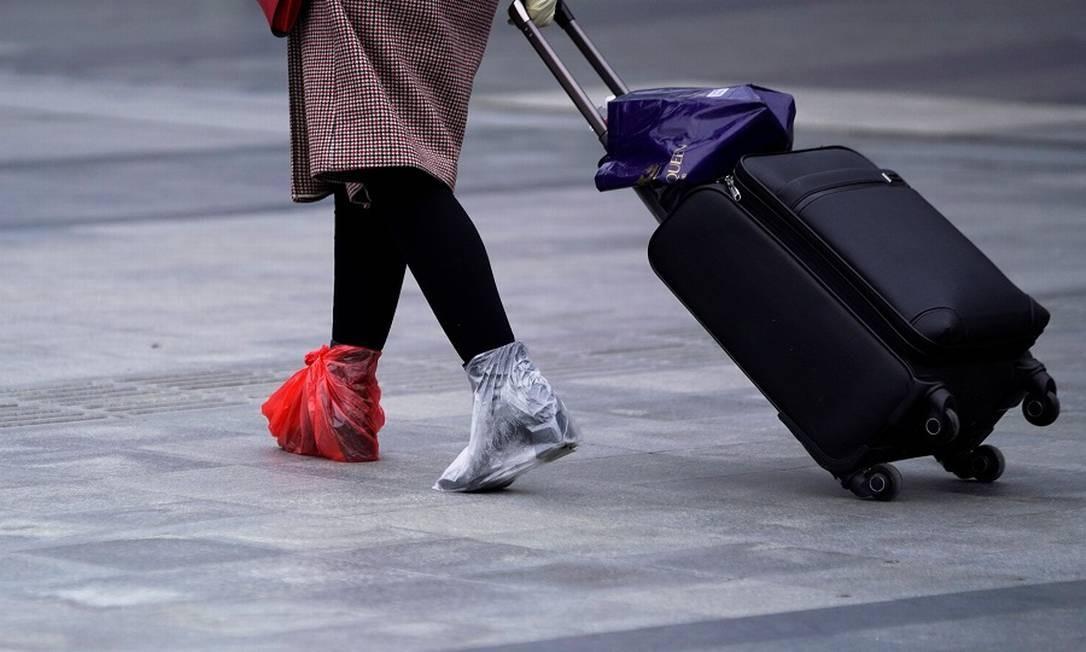 Passageira em estação de trem em Xangai com plástico nos pés para se proteger contra o vírus. Foto: ALY SONG / REUTERS
