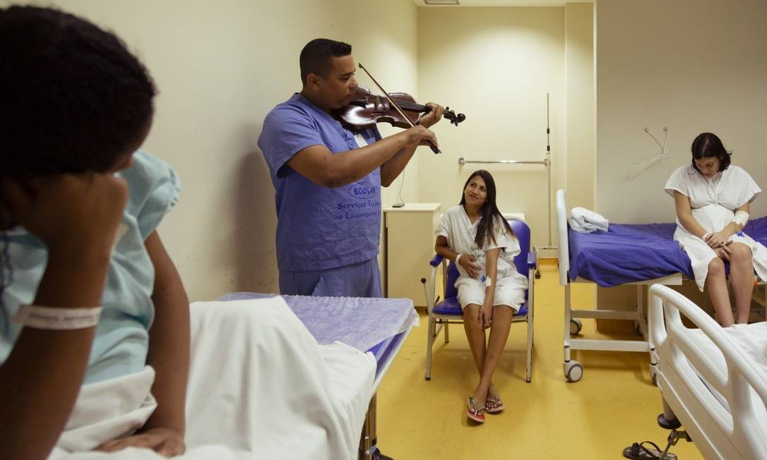 Cláudio Leite toca o instrumento para acalmar as pacientes em hospital de Acari Foto: Leo Martins / Agência O Globo
