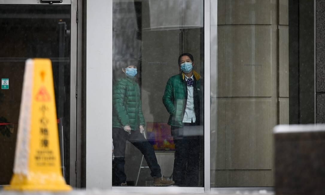Chinesas usa máscaras de proteção em prédio de Beijing. Governo chinês reviu para baixo número de mortes pelo coronavírus Foto: STR / AFP