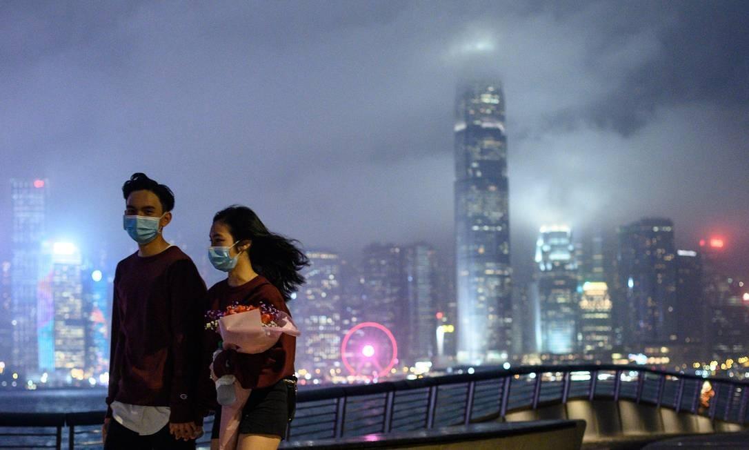 Casal caminha com máscaras por um passeio público na região de Tsim Sha Tsui, em Hong Kong, no dia dos namorados nesta sexta-feira (14) Foto: PHILIP FONG / AFP