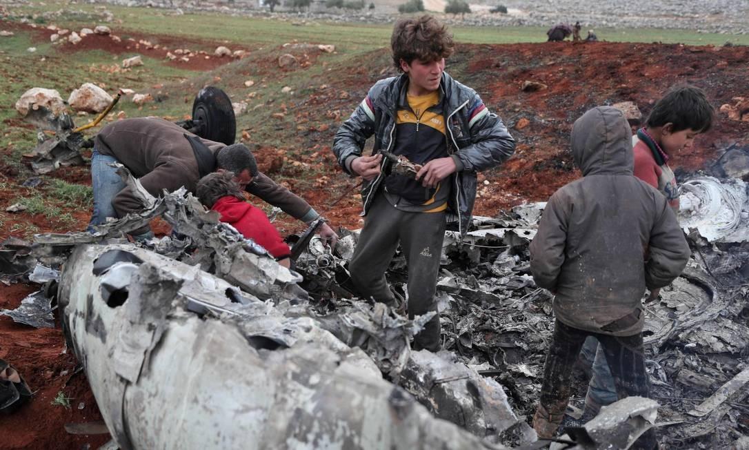 Sírios inspecionam os destroços de um helicóptero militar pertencente a forças do governo depois que ele foi abatido sobre a zona rural ocidental da província de Aleppo. Foto: OMAR HAJ KADOUR / AFP