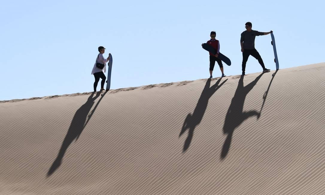 Turistas aproveitam as dunas do oásis de Al Ain Foto: Karim Sahib / AFP