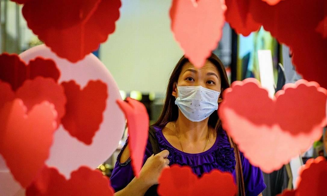 Medo do vírus ocorre não só na China, como também na Tailândia, onde uma mulher com máscara cirúrgica olha uma loja. Foto: MLADEN ANTONOV / AFP