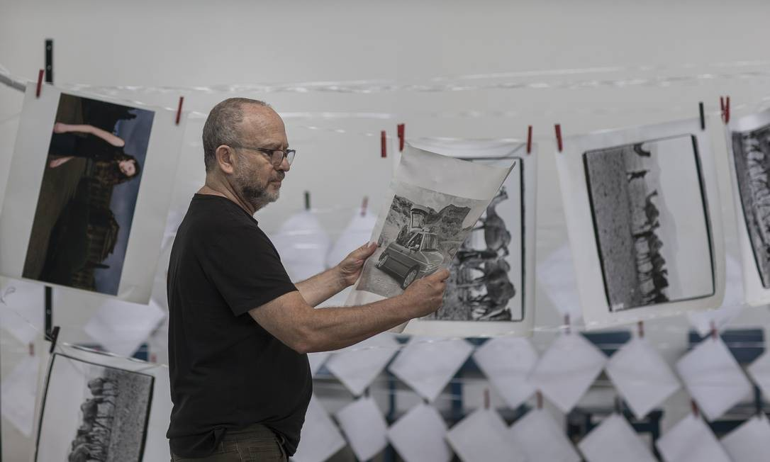 Bob Wolfenson observa fotos atingidas por enchente em seu estúdio em São Paulo Foto: Edilson Dantas / Agência O Globo