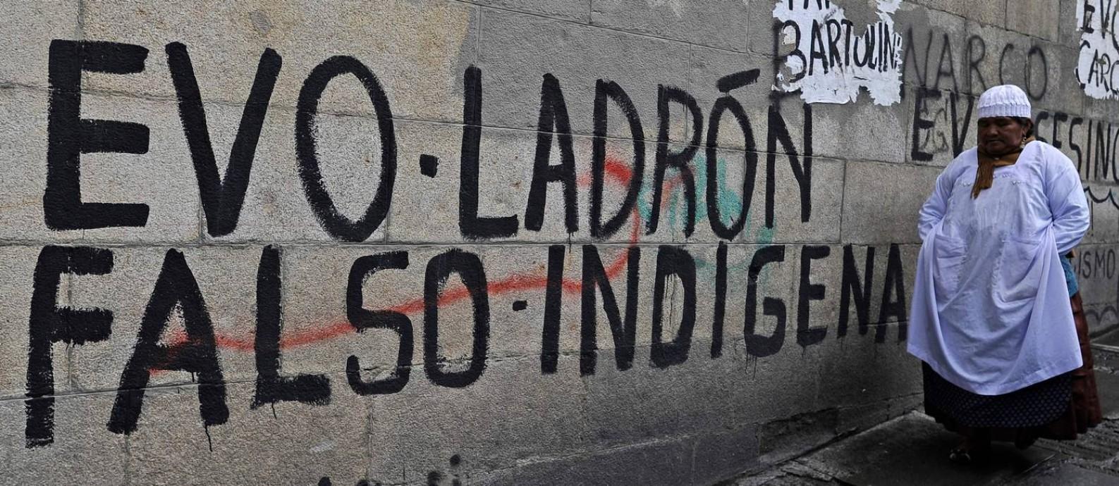 """Mulher passa em frente a pichação em que Morales é chamado de """"ladrão"""" e """"falso indígena"""" em La Paz: nova elite política no poder busca apagar todos os traços dos 14 anos do governo anterior Foto: JORGE BERNAL / AFP"""