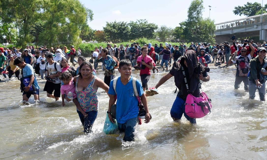 Migrantes centro-americanos que viajam em caravana atravessam o Rio Suchiate, fronteira natural entre Guatemala e México Foto: JOHAN ORDONEZ / AFP/ 20-01-2020