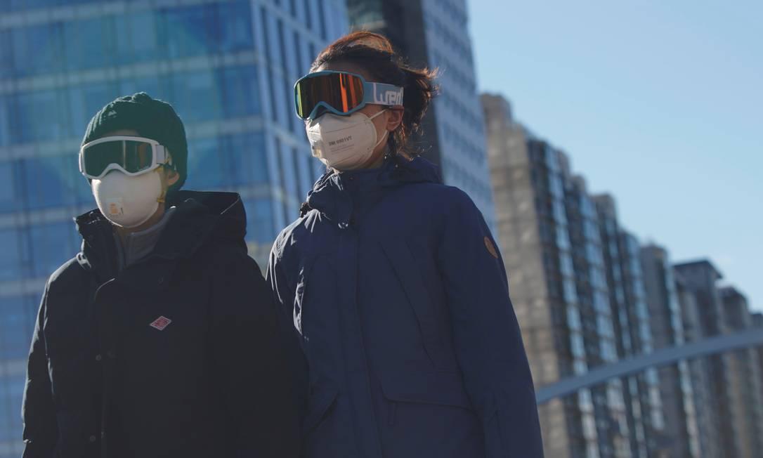 Pessoas usam máscara e óculos de neve no distrito financeiro de Pequim, na China Foto: STRINGER / REUTERS