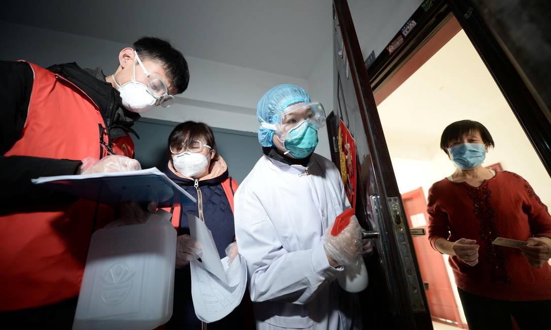 Agentes comunitáros e uma médica inspecionam prédio residencial em Tianjin, na China, para monitorar o estado de saúde dos moradores Foto: CHINA DAILY / REUTERS