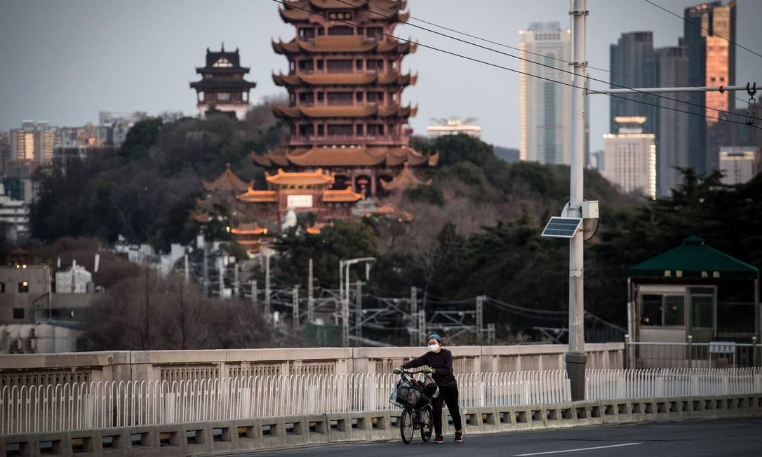 Mulher usa máscara para sair à rua em Wuhan, cidade chinesa onde teve origem a epidemia de coronavírus Foto: STR / AFP