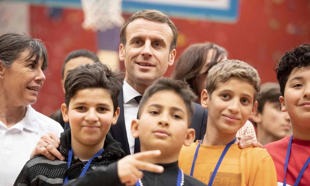O presidente francês, Emmanuel Macron, posa com jovens na visita a Mulhouse durante uma viagem sobre o tema da reconquista republicana e da luta contra o separatismo islâmico, no Leste da França Foto: JEAN-FRANCOIS BADIAS / AFP