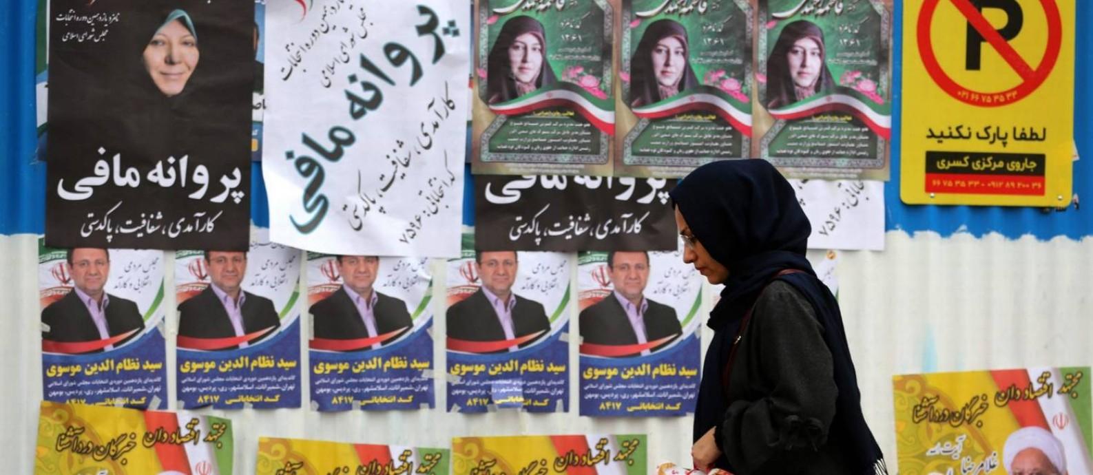 Iraniana passa por cartazes de candidatos no último dia de campanha em Teerã Foto: ATTA KENARE / ATTA KENARE/AFP