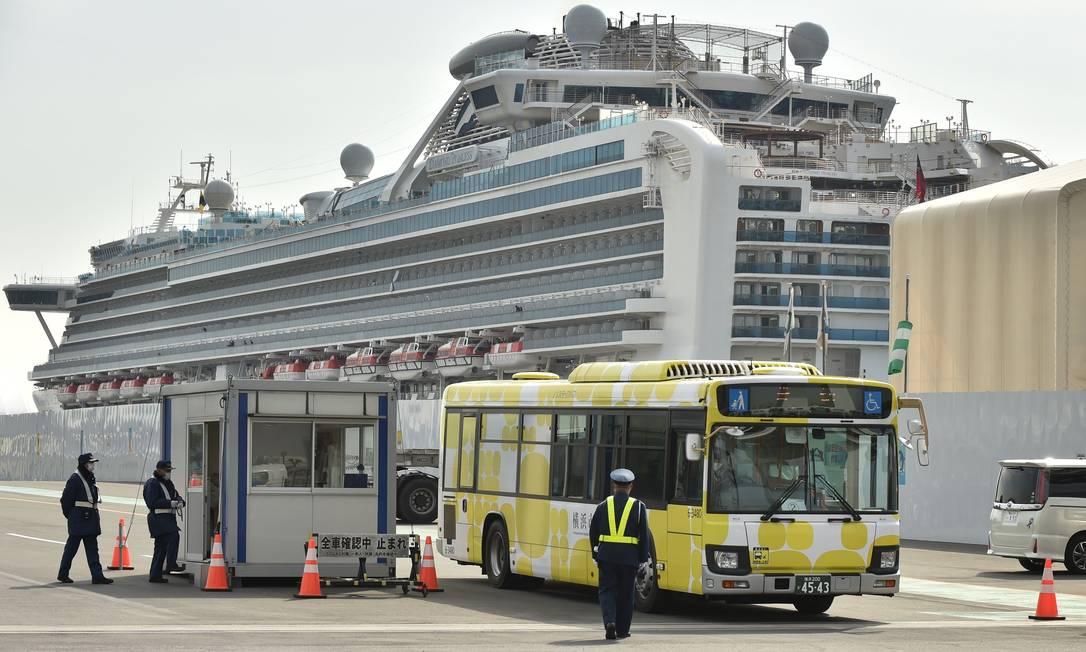 Ônibus deixa o porto de Yokohama com passageiros do Diamond Princess que não foram contaminados. Dois idosos morreram a bordo, segundo uma emissora de TV Foto: KAZUHIRO NOGI / AFP