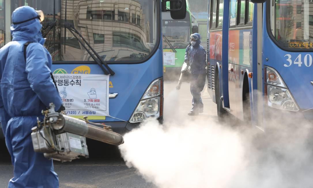 Homens desinfetam ônibus contra o novo coronavírus em terminal de ônibus de Seul, na Coreia do Sul, nesta quinta-feira (20) Foto: - / AFP