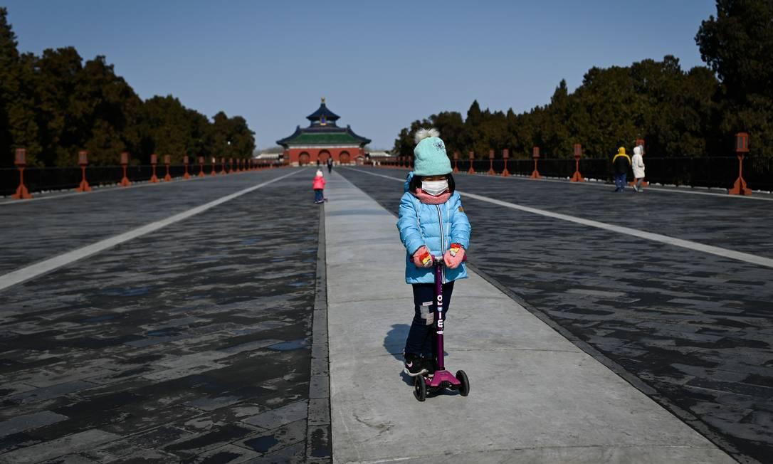 Criança usa máscara protetora enquanto brinca em um parque em Pequim, na China. Foto: WANG ZHAO / AFP