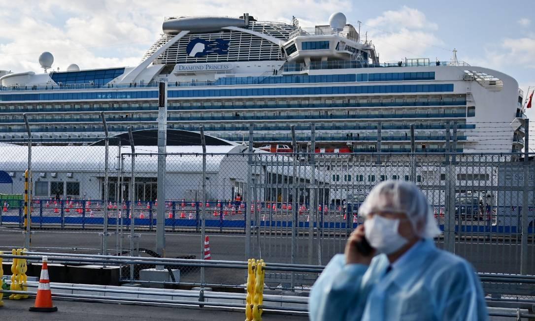 Homem usa máscara protetora em frente ao cruzeiro Diamond Princess, que registrou mais de 600 casos de coronavírus a bordo e ficou ancorado no Japão durante quarentena Foto: CHARLY TRIBALLEAU / AFP