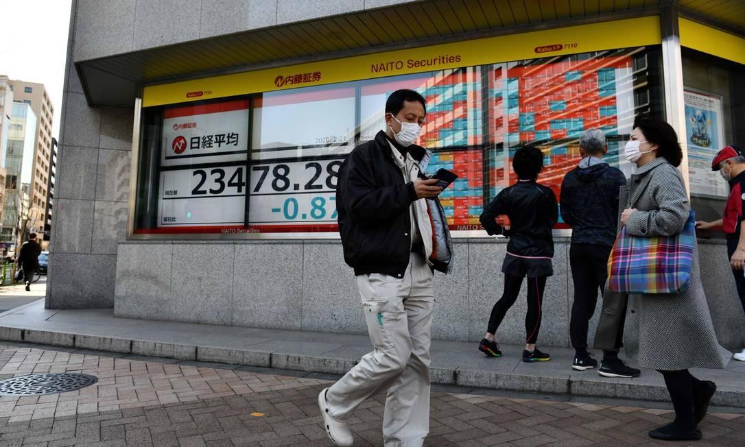 Pedestres usam máscaras de proteção em Tóquio. A capital japonesa deve cancelar eventos abertos para conter o coronavírus Foto: KAZUHIRO NOGI / AFP