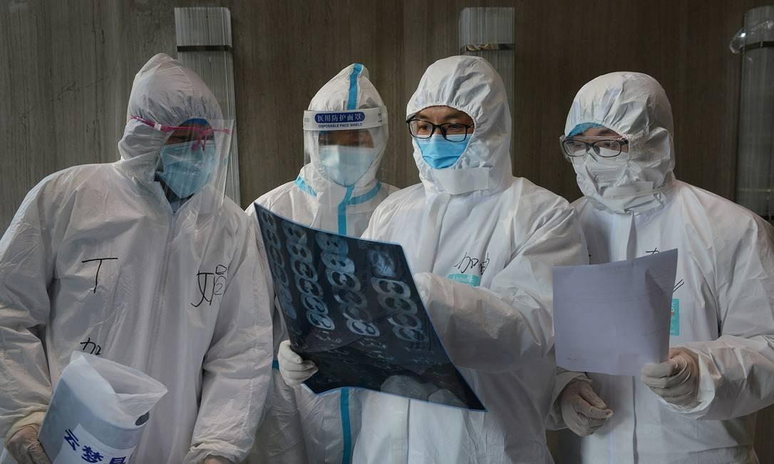 Médicos examinam exame em hospital na China, onde o coronavírus está sendo transmitido por pessoas sem sintomas Foto: CHINA DAILY / REUTERS