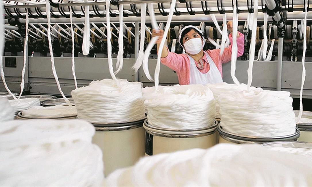 Funcionária em fábrica têxtil em Haian, na China: surto criou grande problema para empresas. Foto: China Daily / Reuters