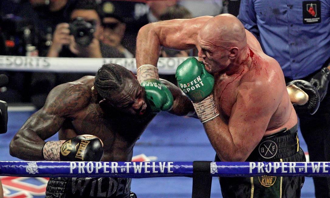Britânico Tyson Fury acerta o americano Deontay Wilder Foto: JOHN GURZINSKI / AFP