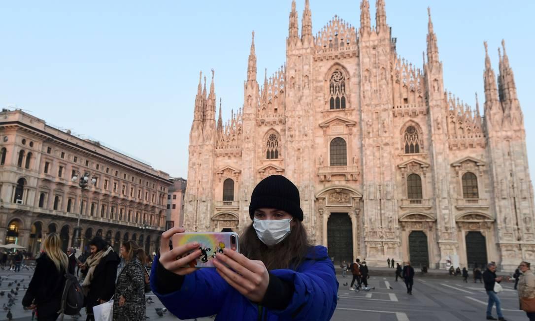 Mulher com máscara faz selfie na Piazza Duomo, no centro de Milão Foto: MIGUEL MEDINA / AFP