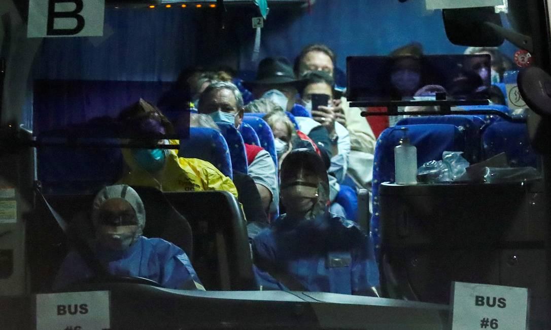 Ônibus carrega passageiros americanos saídos do cruzeiro Diamond Princess, que ficou em quarentena por semanas no Japão, com centenas de contaminados a bordo Foto: Athit Perawongmetha / REUTERS