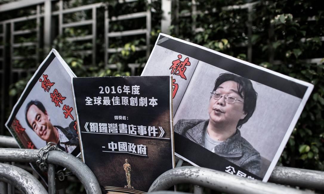 Manifestantes carregam cartazes com os rostos de Gui Minhai e de Lee Bo, seu sócio que também foi preso em 2016 Foto: PHILIPPE LOPEZ / AFP / 19-01-2016