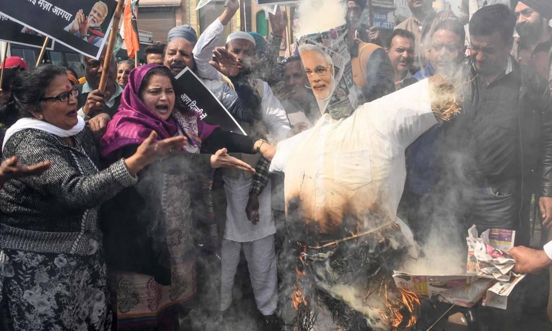 Integrantes de partido de oposição ao governo protestam queimando boneco com rosto do premier Narendra Modi Foto: NARINDER NANU / AFP