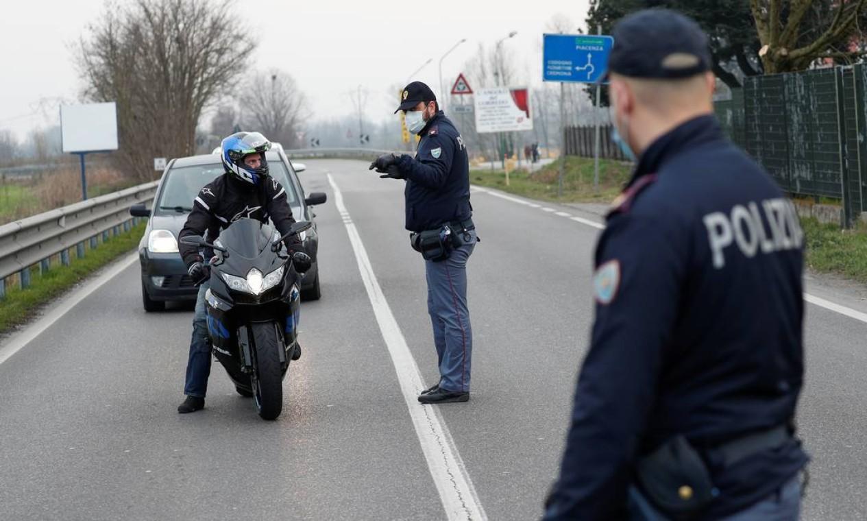 Policiais vestindo máscaras alertam motoristas na estrada entre Codogno e Casalpusterlengo, que foi fechada pelo governo italiano devido a um surto de coronavírus no norte da Itália. Governo já confirmou 11 mortes até esta quarta-feira Foto: GUGLIELMO MANGIAPANE / REUTERS