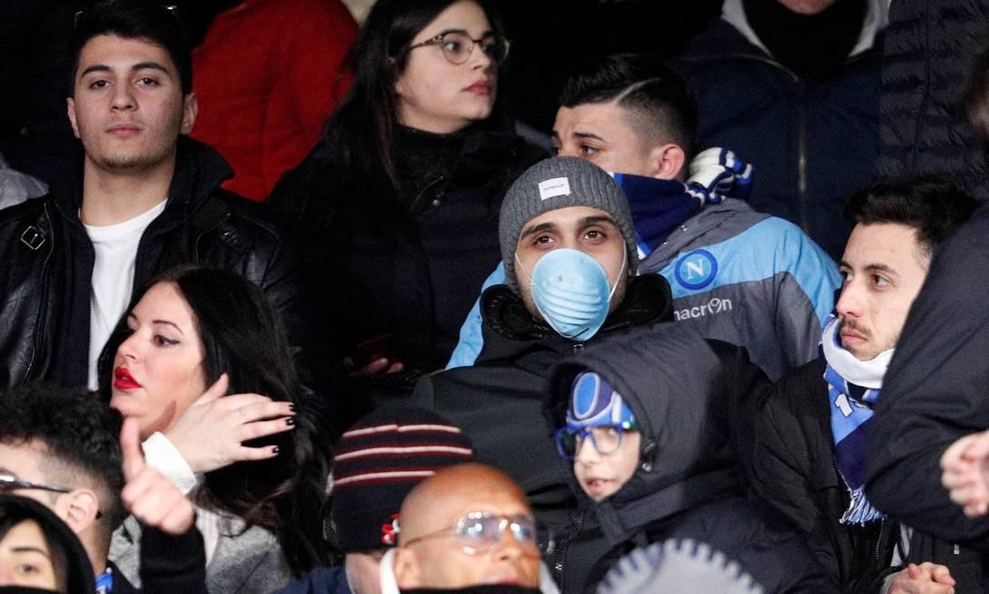 Na partida da noite de terça-feira entre Napoli e FC Barcelona, no Estádio San Paolo, em Nápoles, torcedor usa máscara de proteção. Com mais de 10 mortos na Itália, temor ao vírus cresce Foto: GUGLIELMO MANGIAPANE / REUTERS
