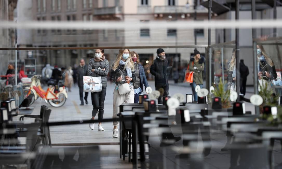 Pessoas caminham pela cidade de Milão, na Itália, usando máscaras Foto: YARA NARDI / REUTERS