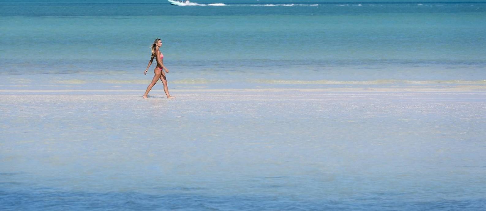 Banhista caminha numa praia da Costa Mujeres, região vizinha a Cancún, no Caribe mexicano Foto: Divulgação