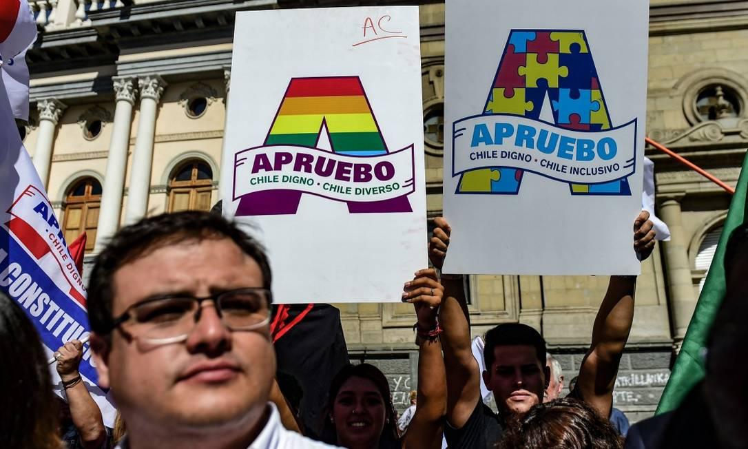 Ativistas carregam cartazes em favor de uma nova Constituição Foto: MARTIN BERNETTI / AFP