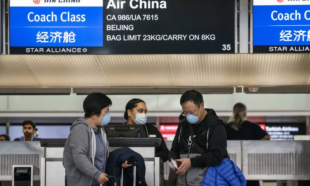O volume de viagens entre São Francisco e a China continental é alto por causa da indústria de tecnologia. Na foto de arquivo, de janeiro deste ano, funcionários e passageiros usam máscaras no Aeroporto Internacional da cidade Foto: David Paul Morris / Bloomberg