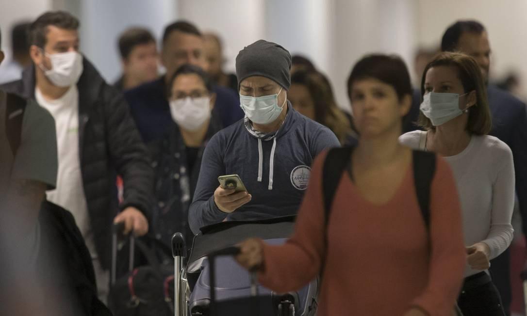 Passageiros desembarcando com máscaras de proteção no Aeroporto Internacional de Guarulhos, em São Paulo Foto: Edilson Dantas / Agência O Globo