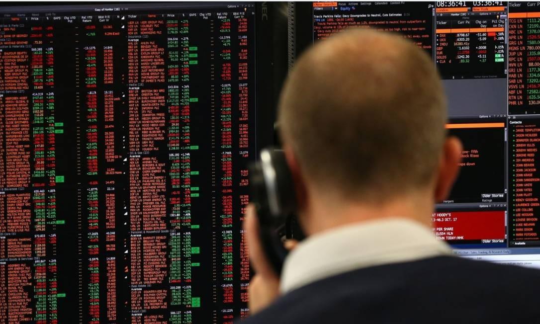 Operador da Bolsa de NY observa painel com desempenho das ações Foto: Bloomberg