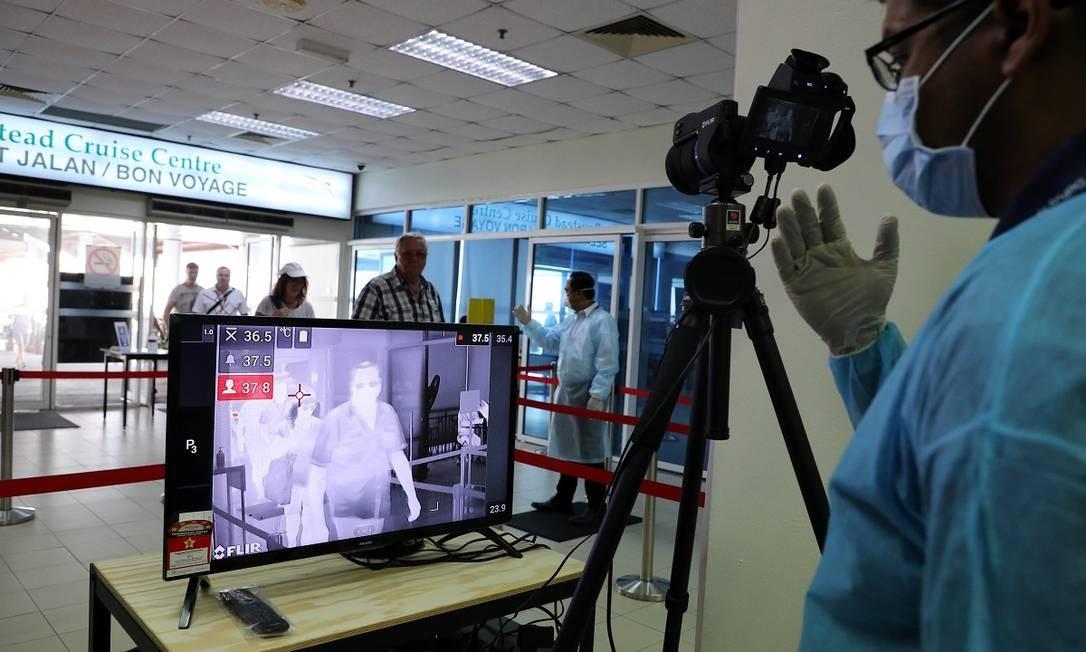 Agente de saúde verifica temperatura de passageiros no terminal de cruzeiros em Port Kiang, na Malásia Foto: Lim Huey Teng / Reuters