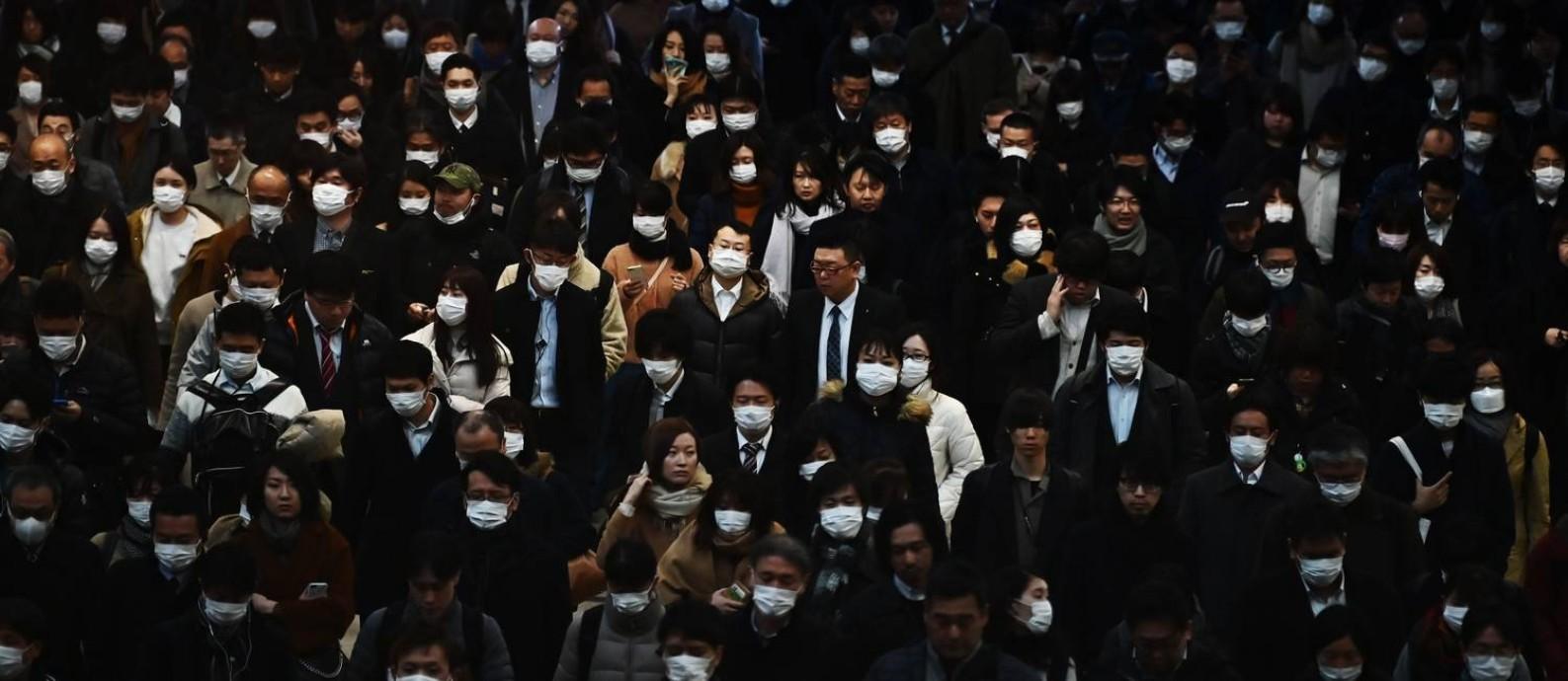 No horário do rush, japoneses esperam para pegar o trem para o trabalho na estação de Shinagawa, em Tóquio. Foto: CHARLY TRIBALLEAU / AFP