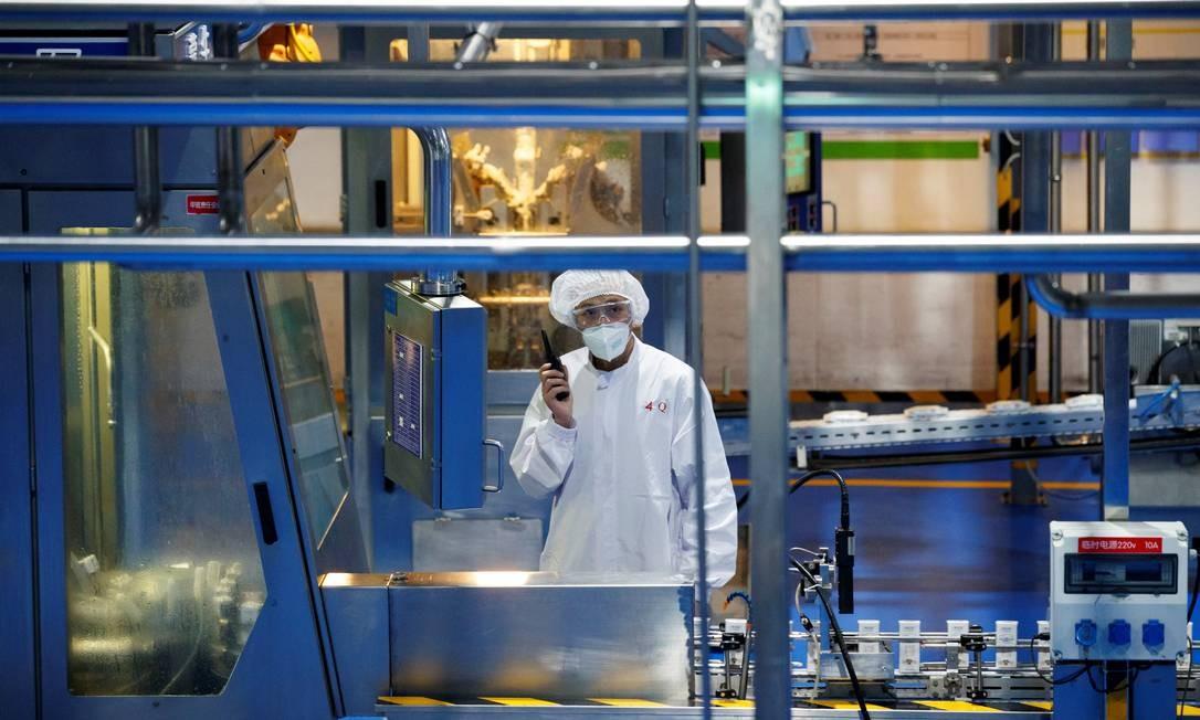 Trabalhador usa máscara de proteção em fábrica de Pequim Foto: THOMAS PETER / REUTERS